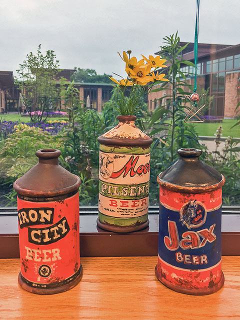 Three ceramic beer cans on a windowsill