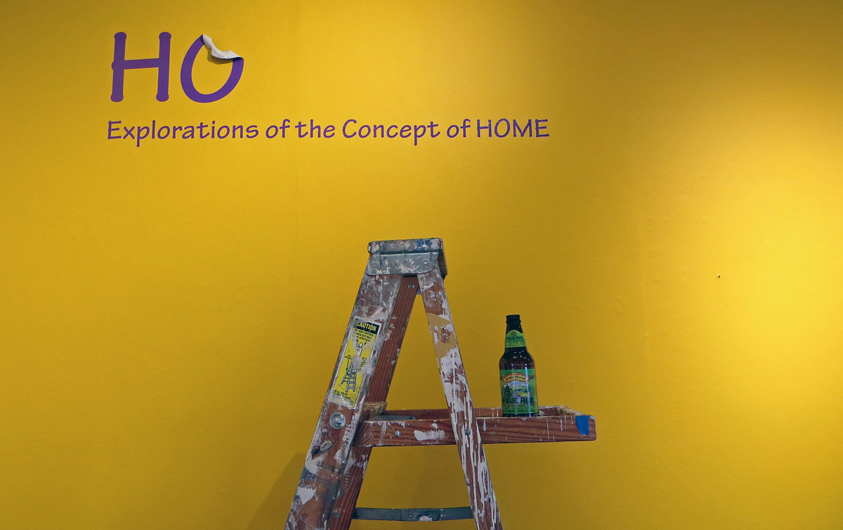 Ladder with beer in front of wall title being de-installed