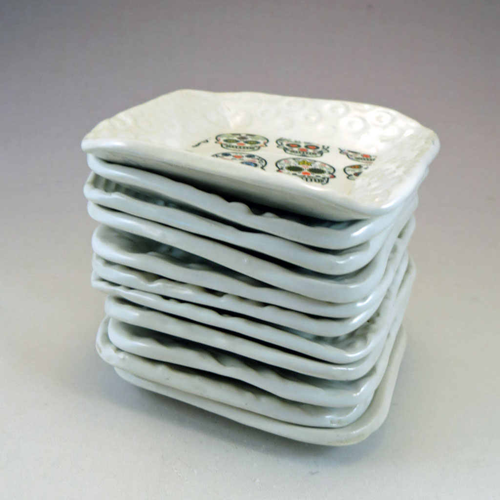 Stack of white dishes with sugar skulls